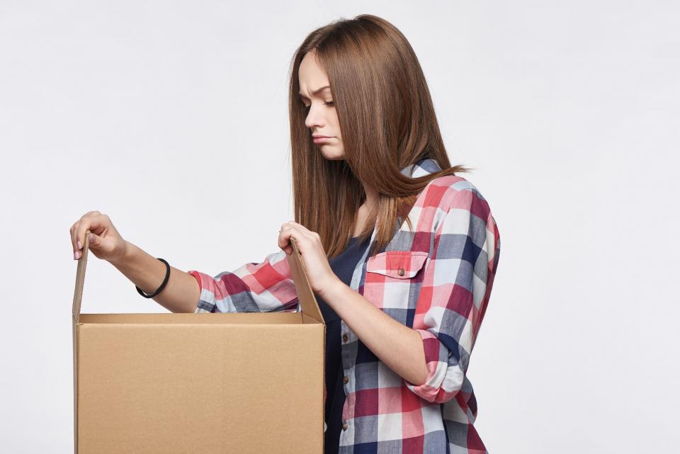 Junge Frau blickt enttäuscht in ein geöffetes Paket
