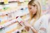Frau studiert im Supermarkt die Gesundheitsversprechen eines Getränks